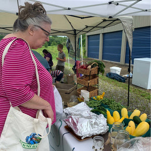 A woman with a tote bag looks at a table of fresh farm vegetables