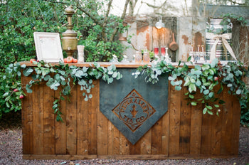 A wide wooden bar decorated with leaves and a metal Piper & Leaf sign