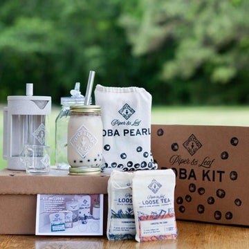 A boba kit box on a table with its content - a tea press, jars, boba pearls, and two bags of loose leaf