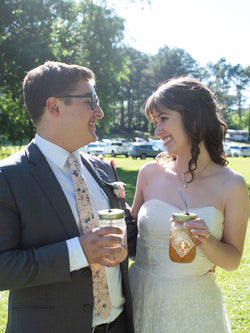 A bride and groom smile at each other as they hold Piper & Leaf pint jars of tea.