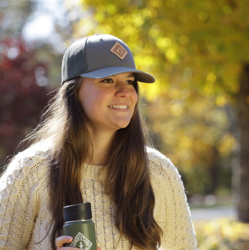 A young woman smiles while wearing ball cap with a leather Piper & Leaf logo