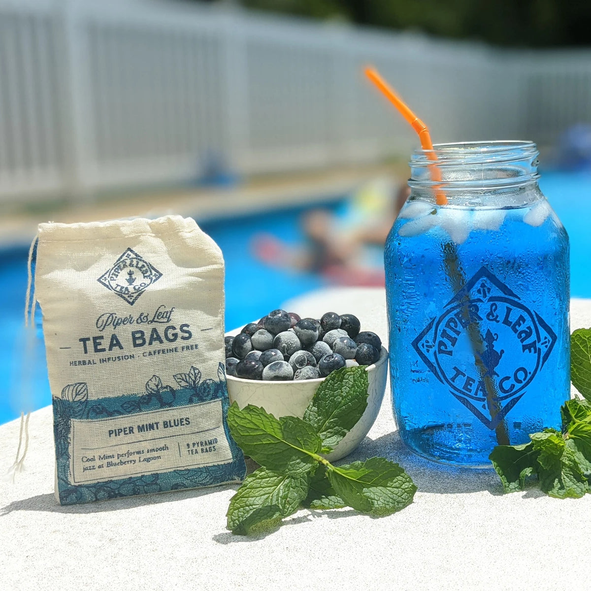 A bag of Piper Mint Blues, blueberries, mint, and a jar of blue iced tea