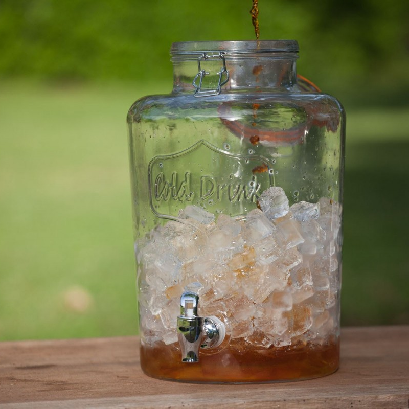 A glass dispenser full of ice with tea pouring into the top
