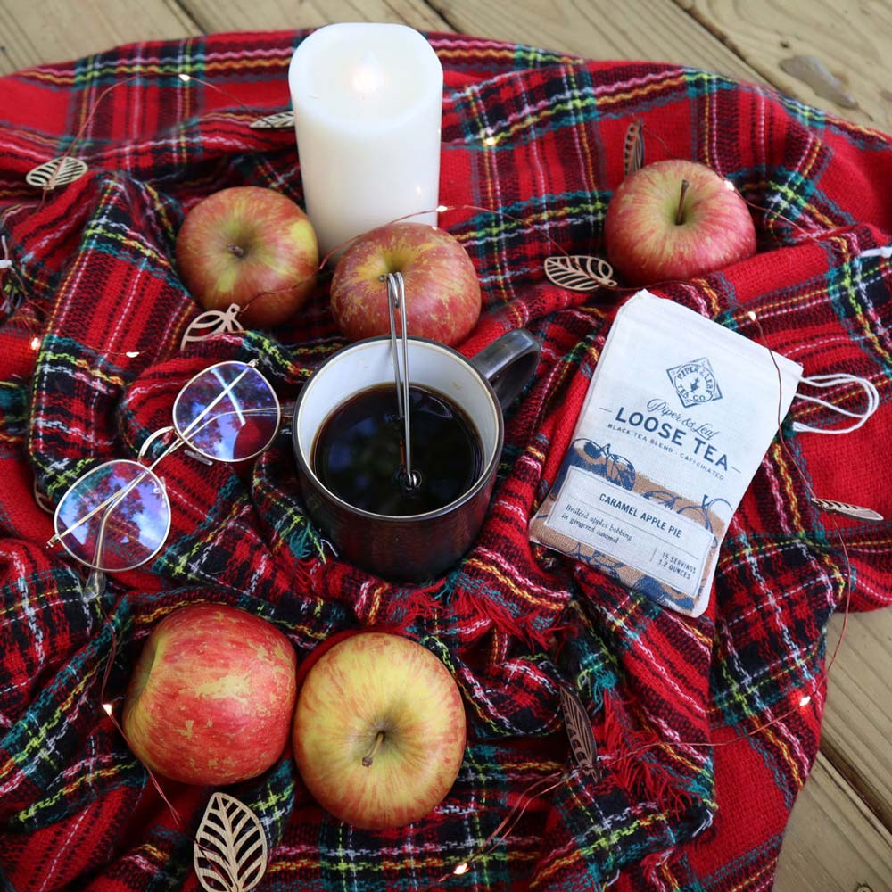 A mug of tea on a plaid blanket, surrounded by apples, bags of tea, and fall decor