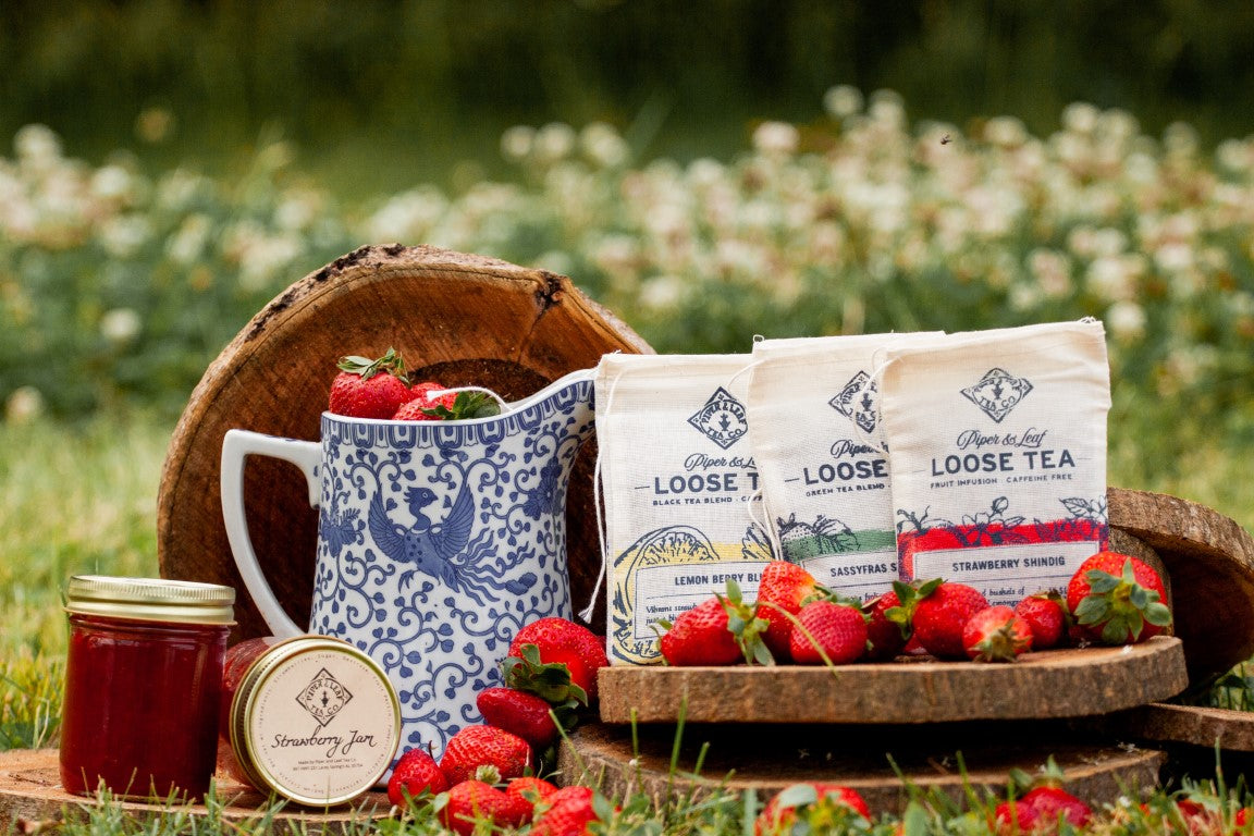 Jars of jam and 3 bags of tea rest amid dozens of fresh strawberries