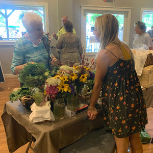An older woman talks to the young woman selling flower bouquets
