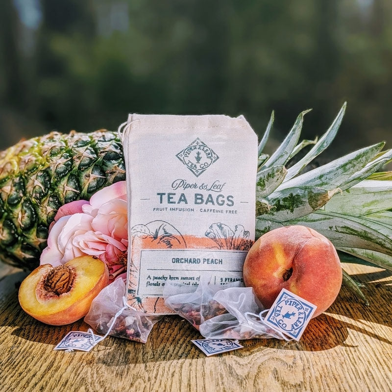 An Orchard Peach bag with pineapples, peaches, roses, and scattered tea bags