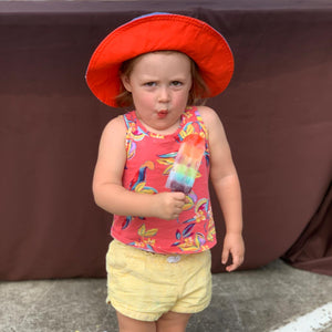A little girl makes a silly face while holding a rainbow popsicle