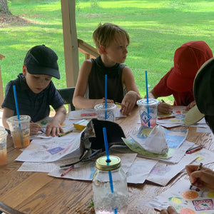 Kids coloring at a table covered in coloring pages and cups of tea