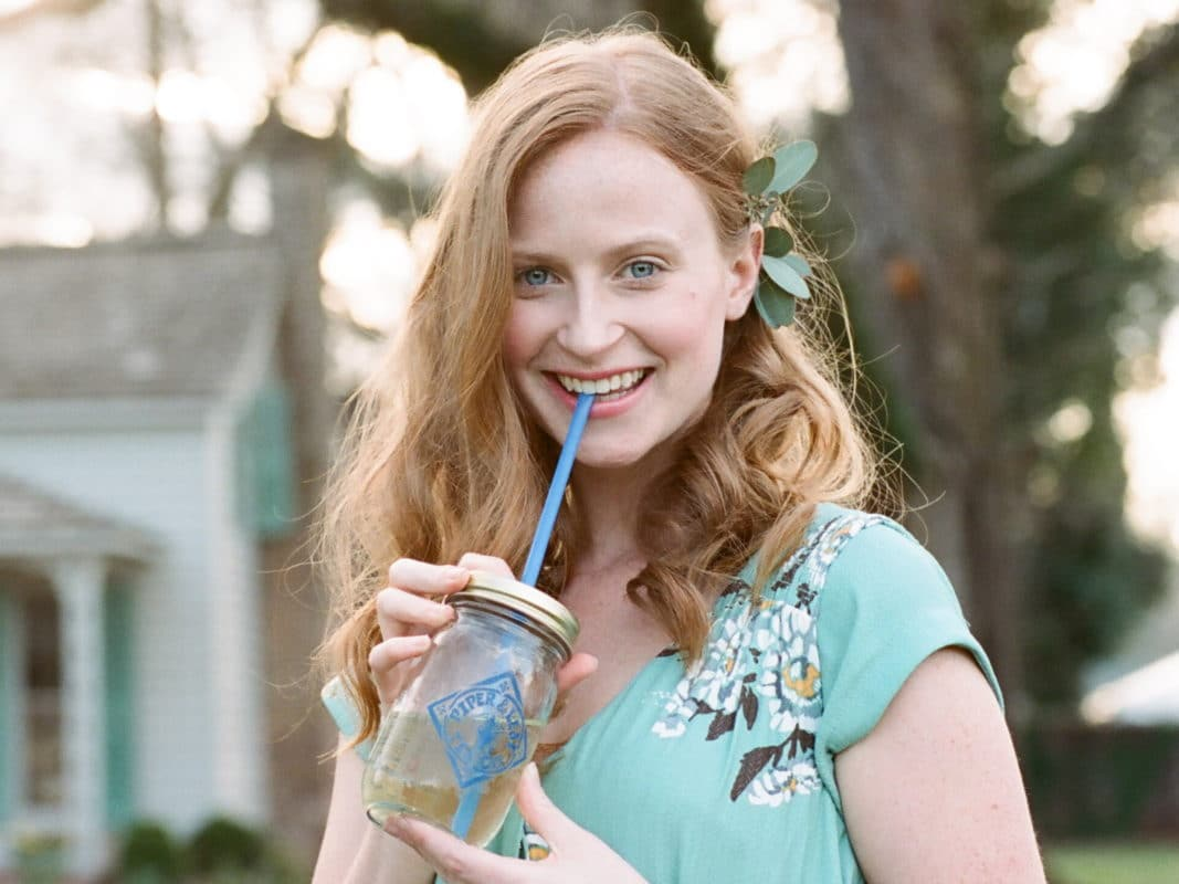 A young woman with red hair sips from a pint jar of pale tea
