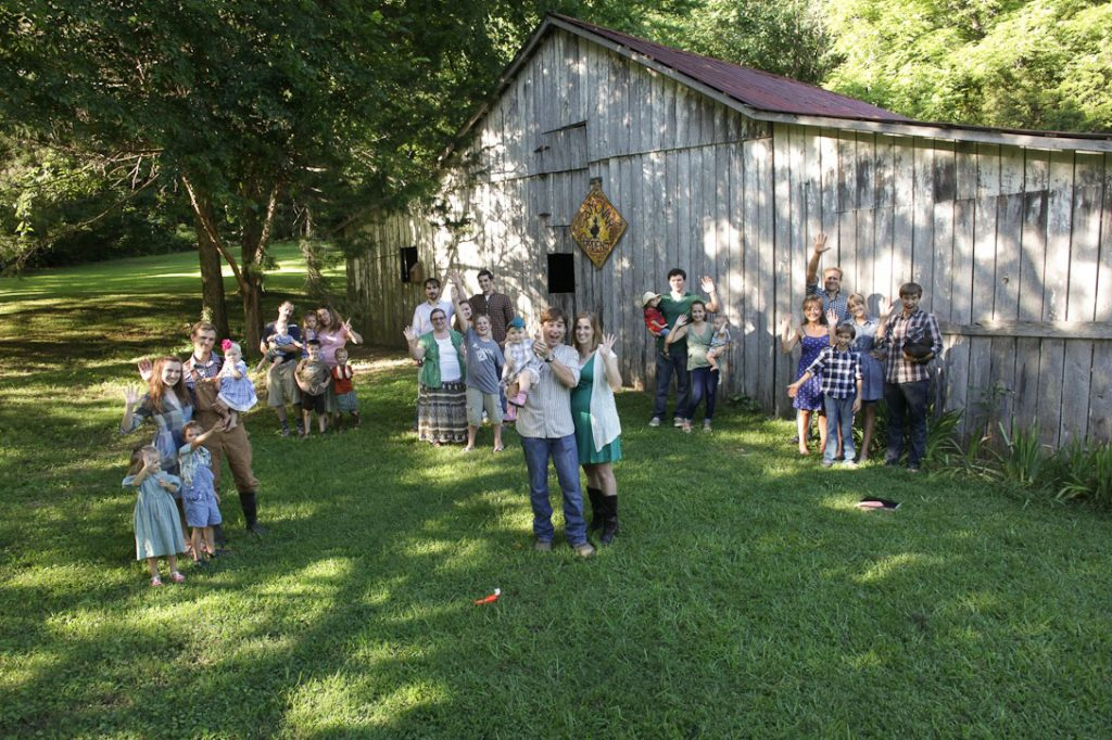 Several groups of family members hang out in the yard near a barn