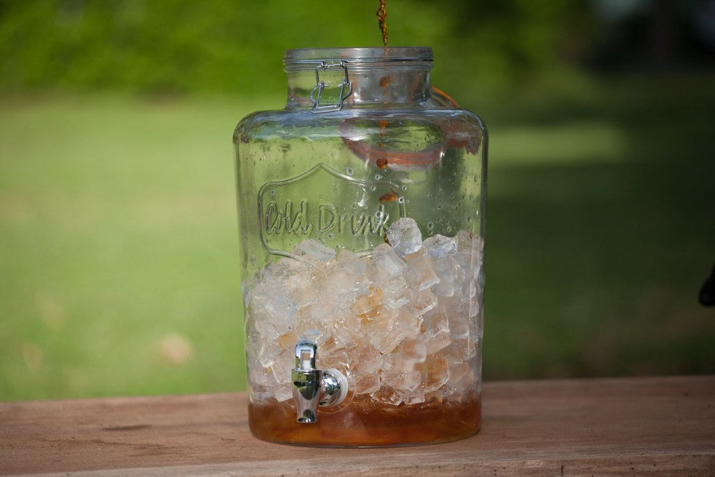 A large glass dispenser of ice being filled with sweet tea