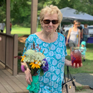 An older woman carrying a bouquet of fresh flowers and a quart jar of tea