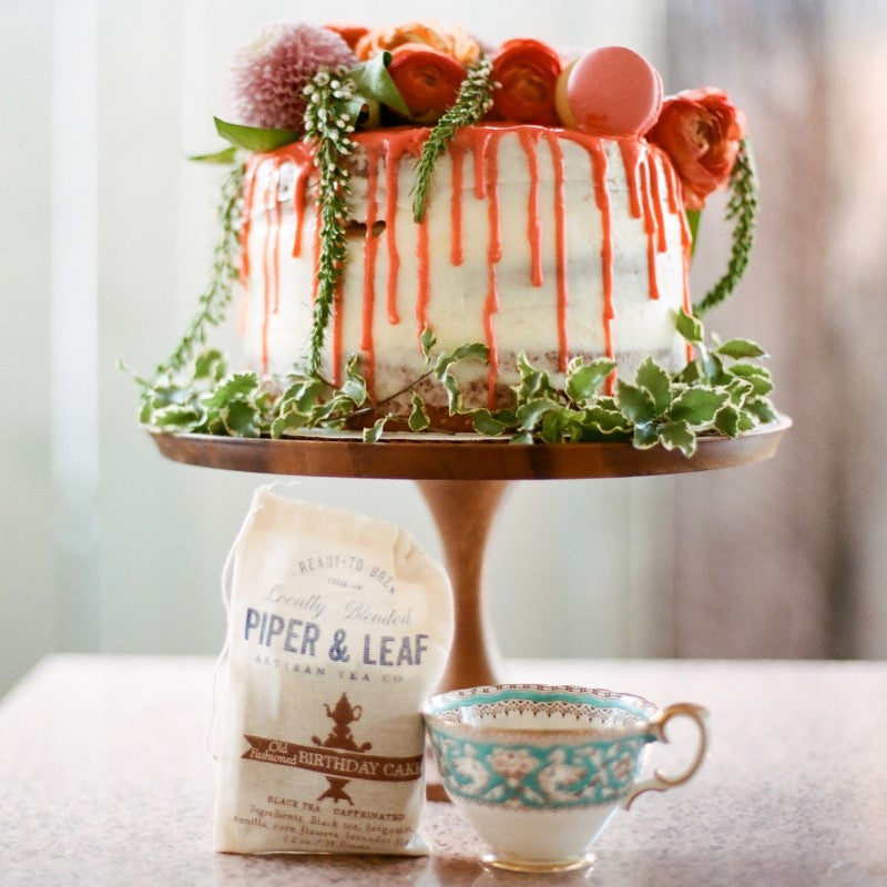 A colorful cake on a stand over a teacup and a bag of Old Fashioned Birthday Cake