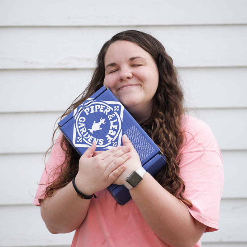 A young woman in a pink shirt hugging a blue box printed with the Piper & Leaf logo