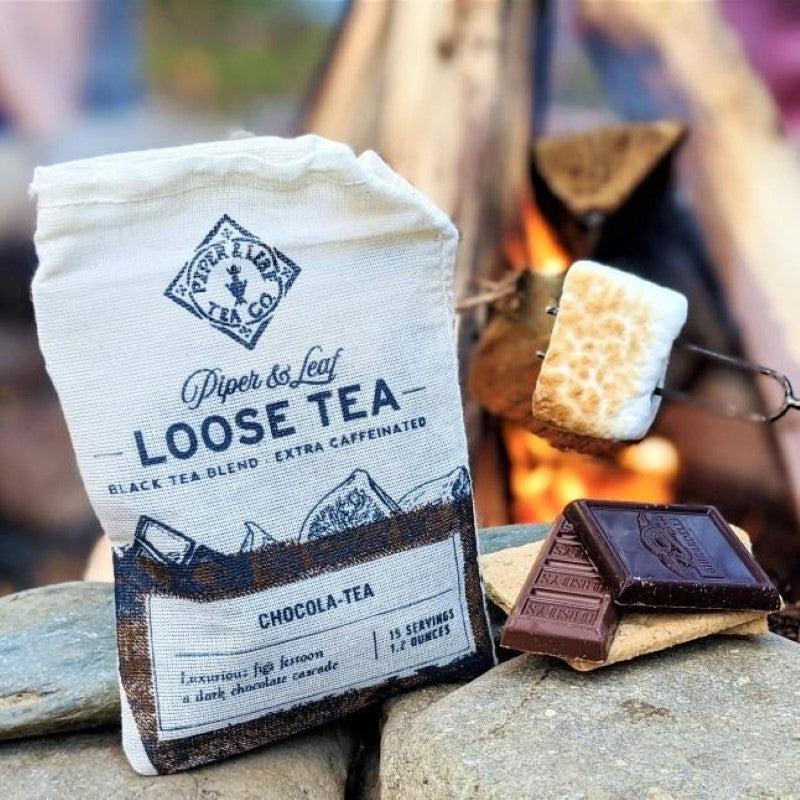 A bag of Chocola-Tea loose leaf sits in front of the fire with s'mores