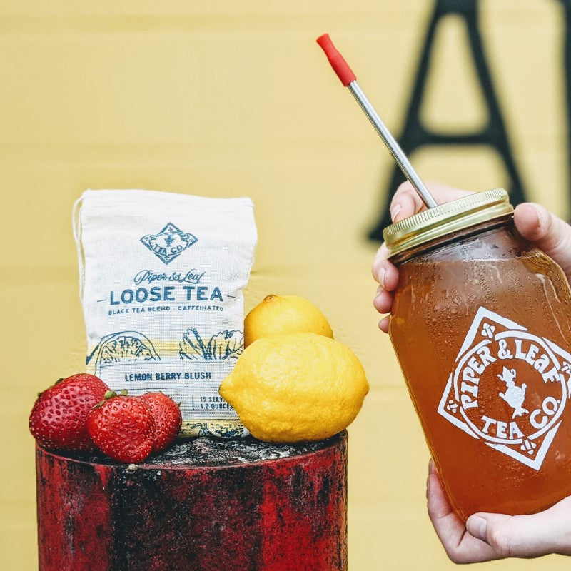 Lemon Berry Blush bag with strawberries, lemon and hands holding a jar of iced tea