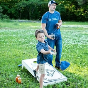 A young boy and his dad throw bean bags at a cornhole board