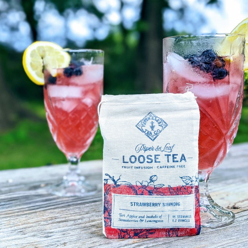 Two glasses of pink iced tea behind bag of Strawberry Shindig