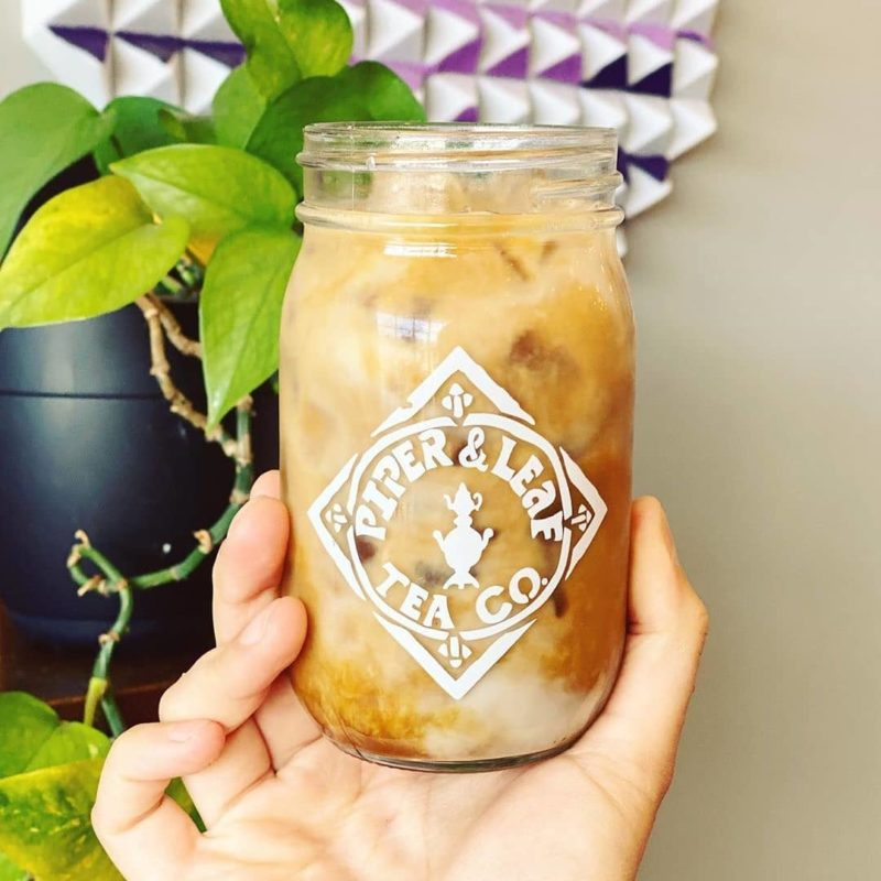 A close up of a Piper & Leaf pint jar filled with coffee and creamer