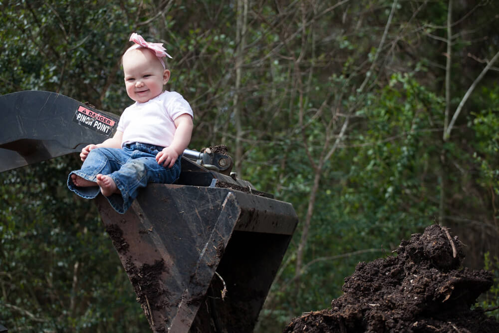 A baby with a bow on sitting on top of an excavator