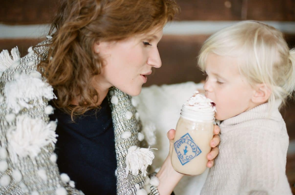A mother offers a jar overflowing with whipped cream to her toddler