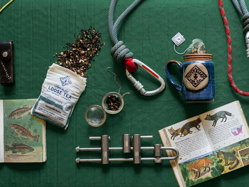 A bag of Trailblazer Blend tea spilled out next to camping supplies, a field guide, and a blue mug