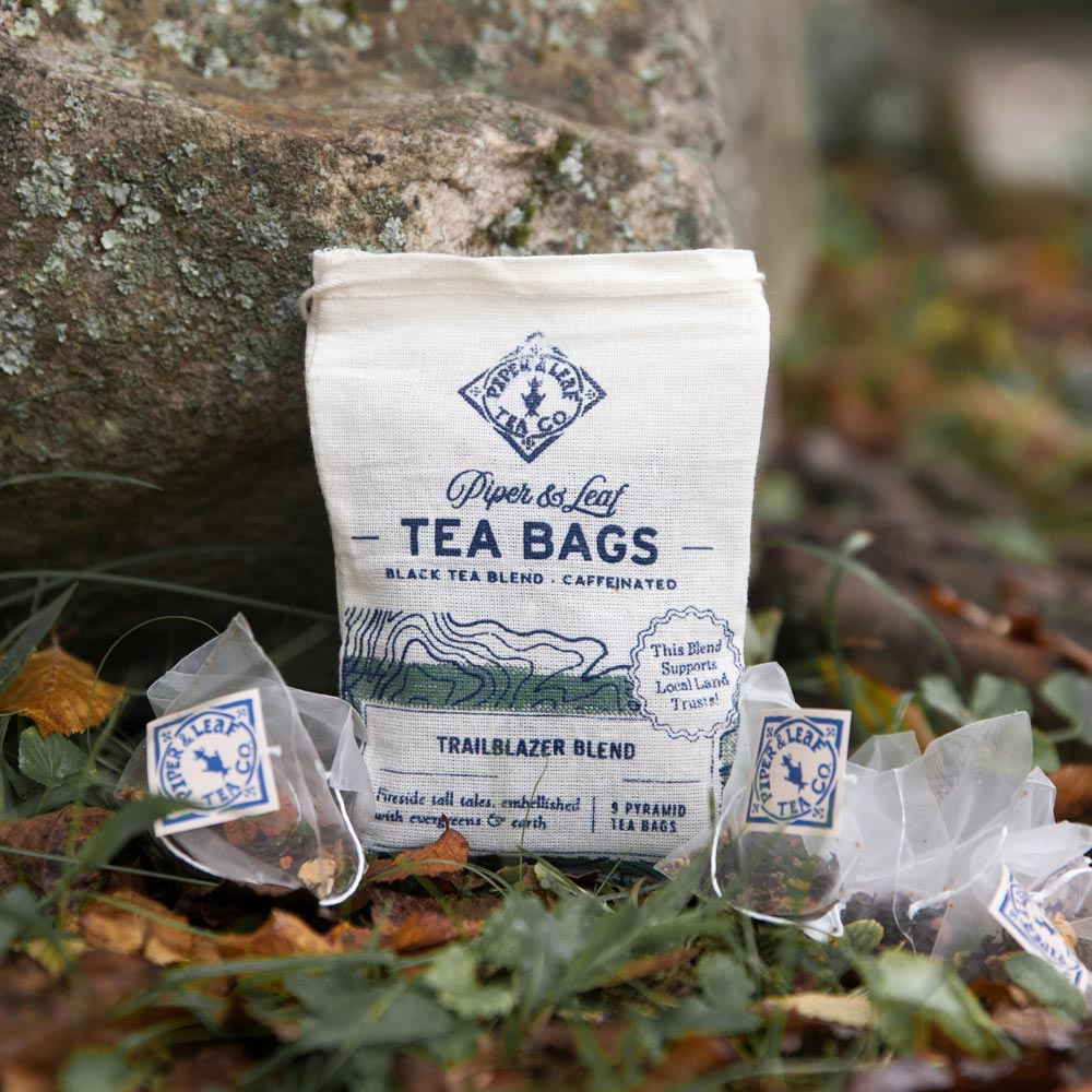 A muslin bag of Trailblazer Blend on a forest floor, surrounded by tea bags