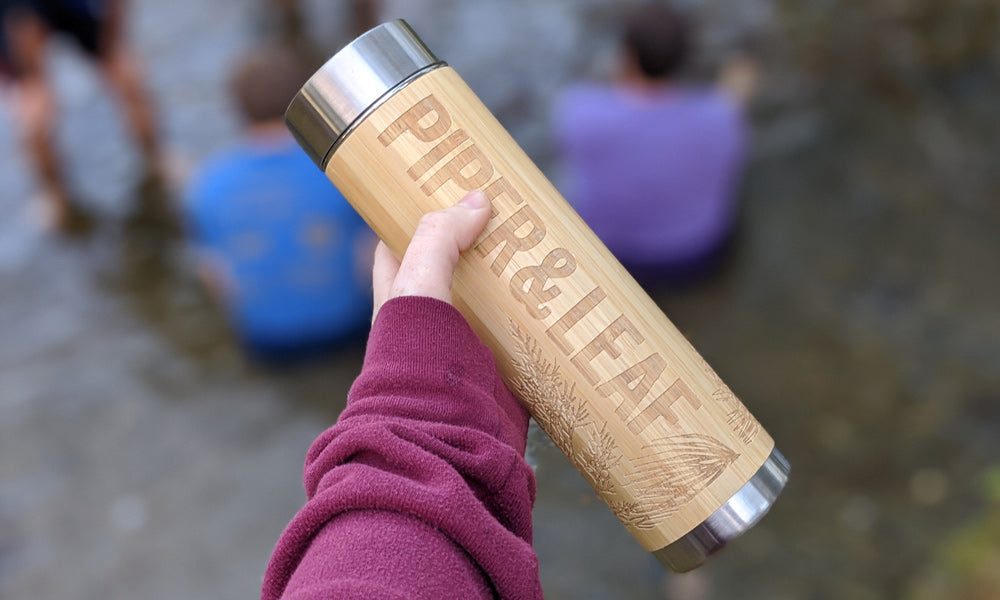 An arm in a red sweatshirt holds out a bamboo tumbler engraved with