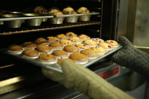 Someone wearing mitts and removing a freshly baked tray of muffins from an oven.