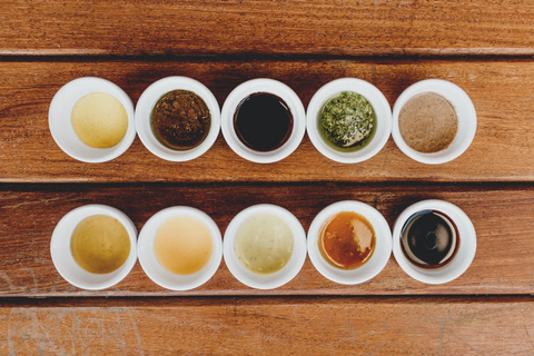Ten small cups of different sauces.