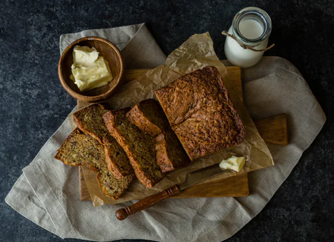 Cut banana bread slices with a small bowl of butter and a glass of milk.