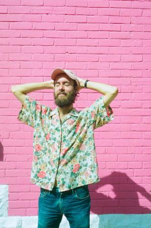 Picture of Eliott wearing a printed floral button up and a baseball cap, his hands are placed relaxed behind his head. He stands in front of a pink wall, closing his eyes as the sun hits him.