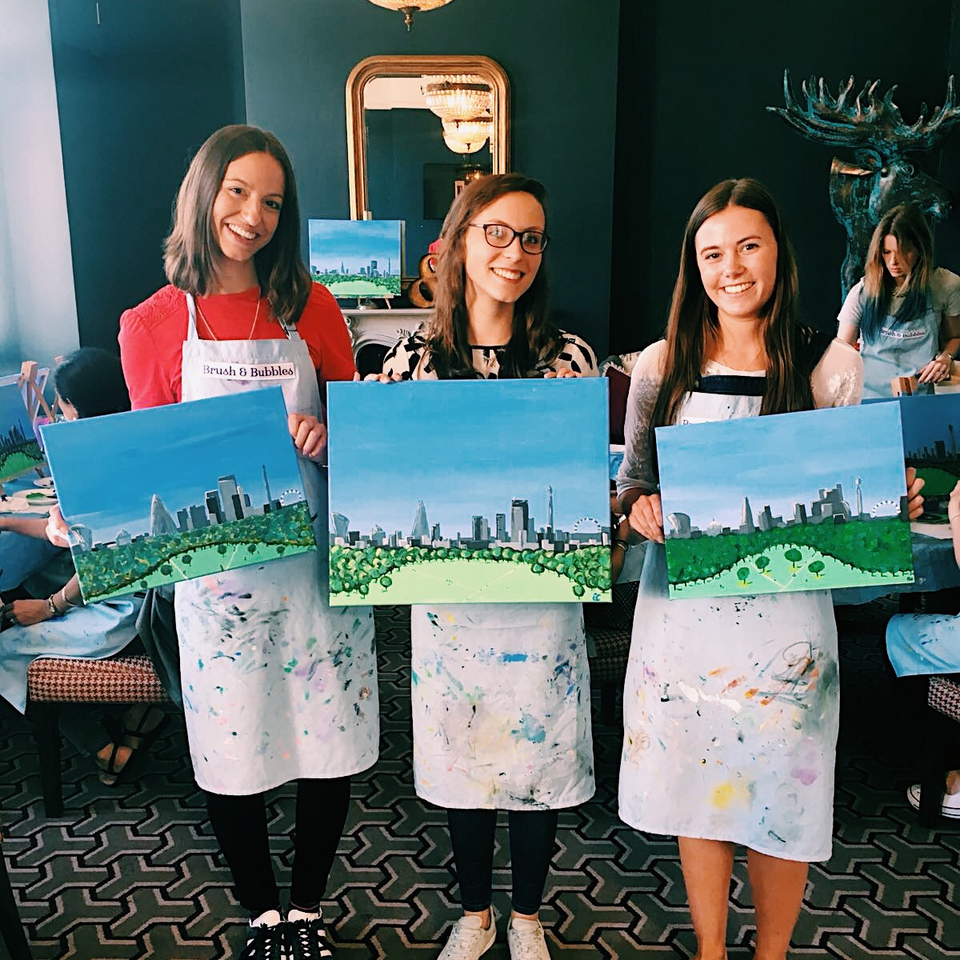 three women posing with their Greenwich Park landscape paintings