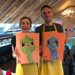 Couple poses for photo with Emu painting for a fun date night activity