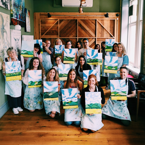 group posing with their paintings during a corporate painting team bonding event