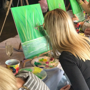 woman learning to paint a pond scene during acrylic art class