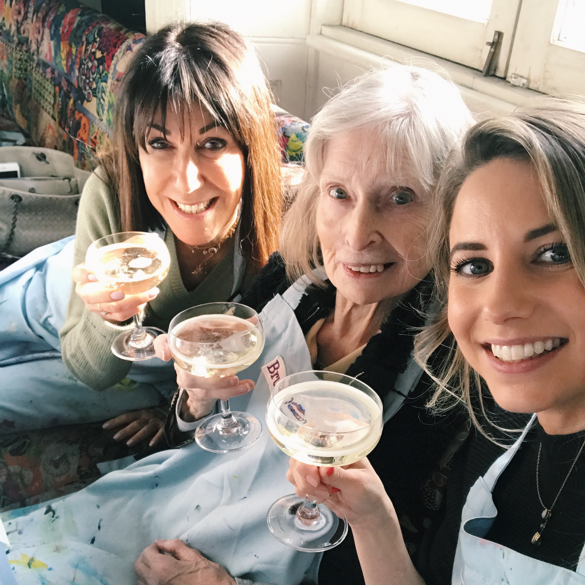 family enjoying a glass of prosecco during a painting class