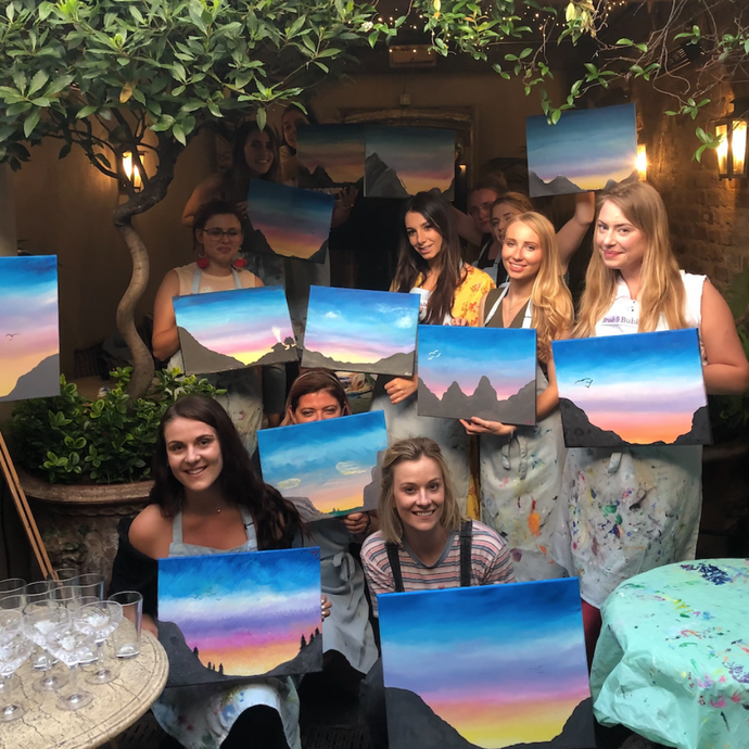 group of women holding their sunset silhouette paintings