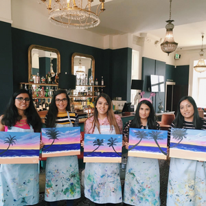 woman holding their palm tree sunset paintings for hen do celebration