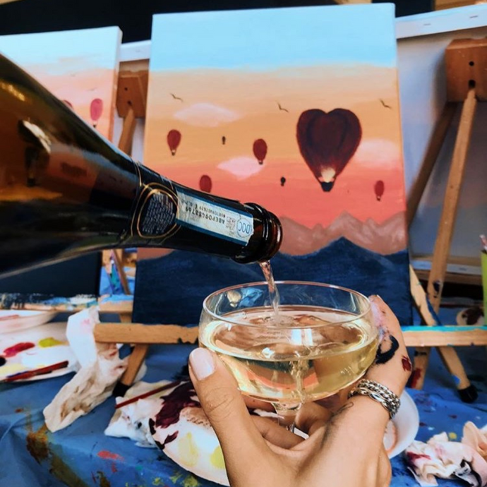 glass of prosecco being poured in front of a hot air balloon painting