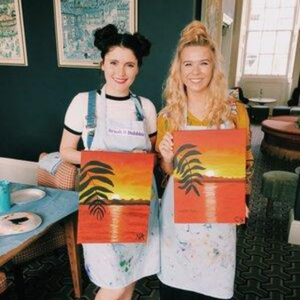 two girls holding their sunset paradise paintings