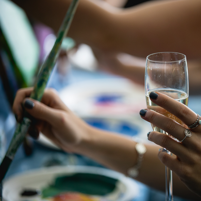 woman holding a paint brush and glass of prosecco
