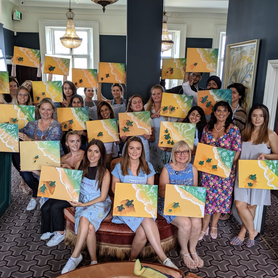 step by step painting class holding their turtle beach canvases