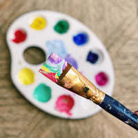 paint brush covered with brightly coloured paints