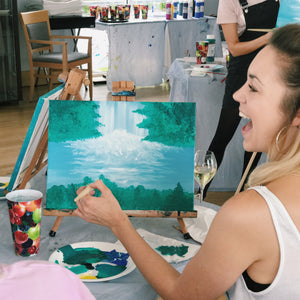 Girl laughing whilst painting a waterfall