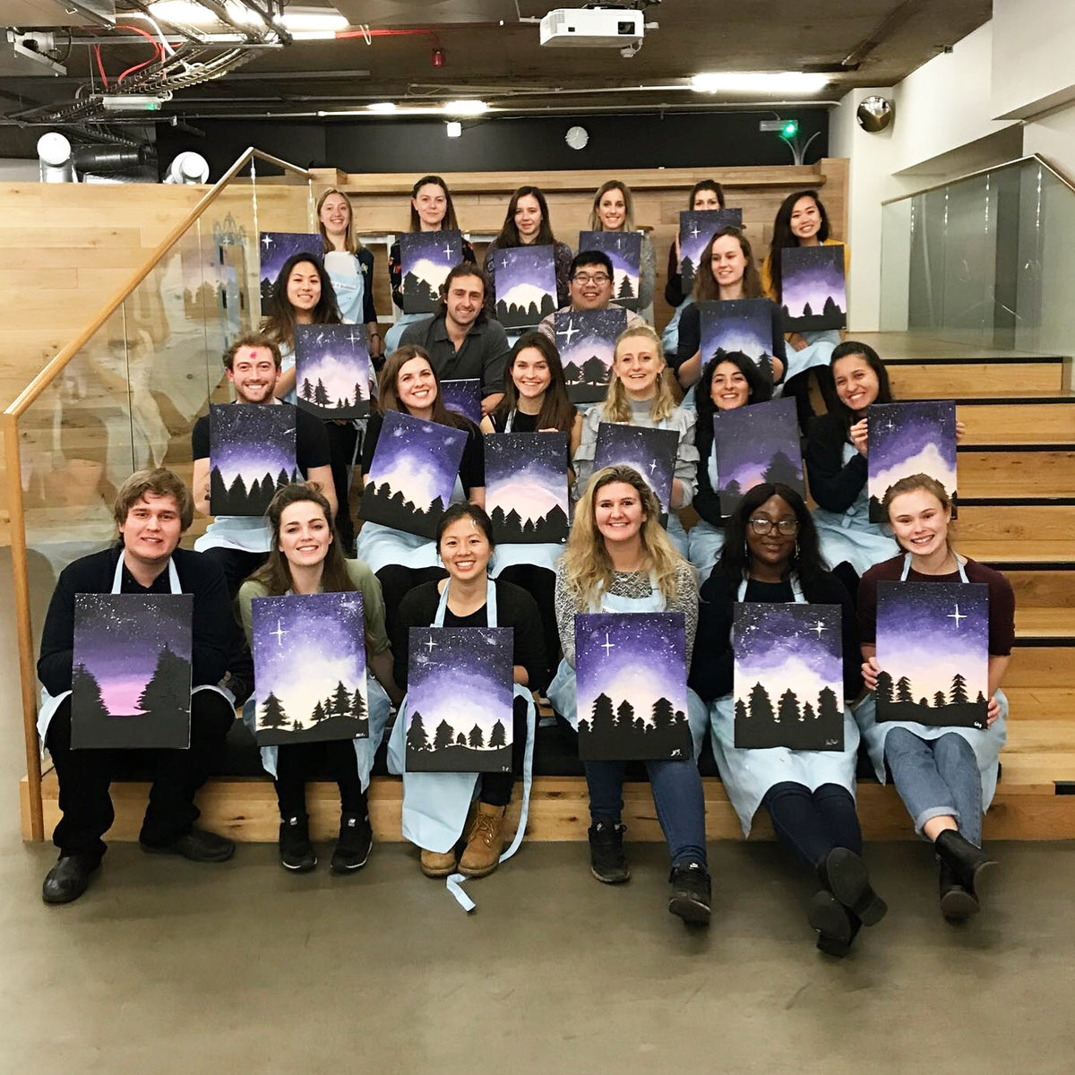 office employees posing with their acrylic paintings