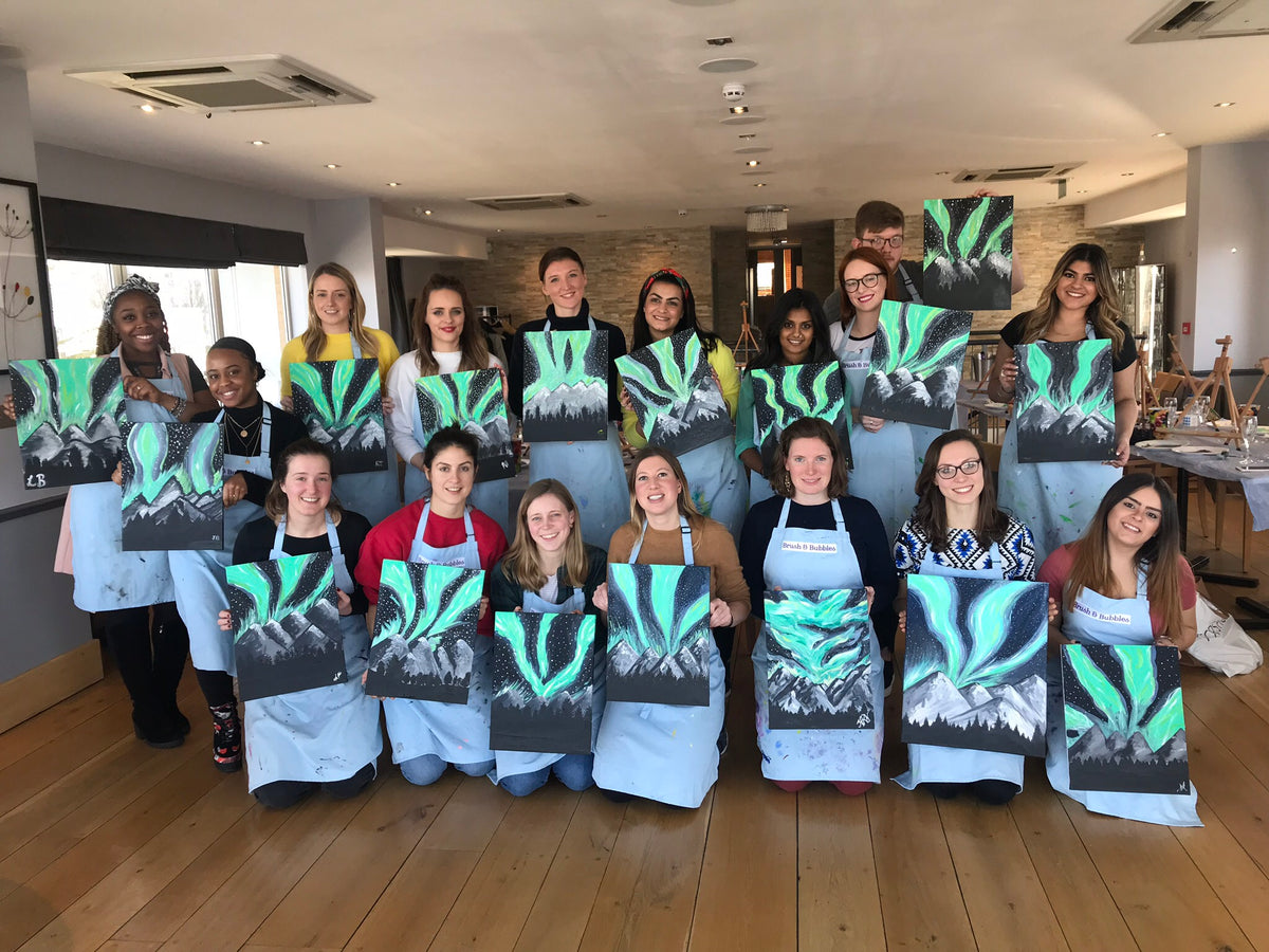 painting class holding their acrylic canvas northern lights paintings