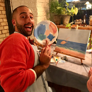 Man poses with art palette after mixing paints together for his canvas painting