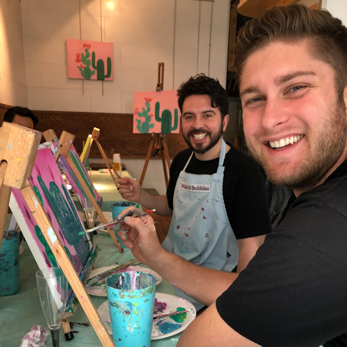 Friends smiling whilst learning to paint a canvas